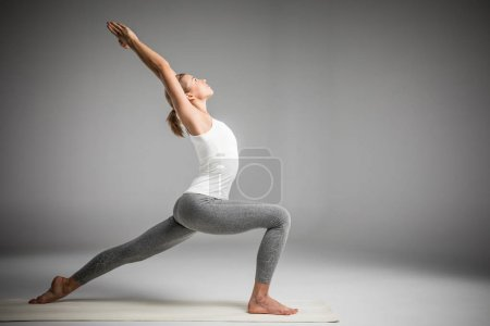 Photo for Woman practicing yoga standing in variation of Warrior I posture or Virabhadrasana One pose  isolated on grey - Royalty Free Image