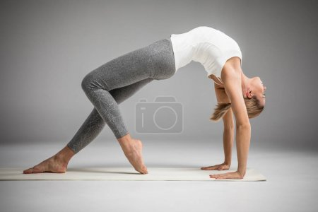 Photo for Woman practicing yoga performing Bridge pose (Ekopada Dhanurasana) on yoga mat  isolated on grey - Royalty Free Image