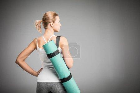 Sportswoman holding yoga mat