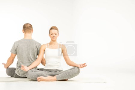 Photo pour Young couple practicing yoga sitting in lotus position on yoga mats  isolated on white - image libre de droit