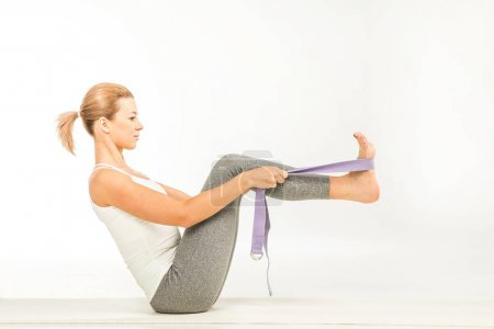 Woman practicing yoga with strap