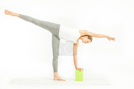 Photo pour Sportswoman standing on yoga mat and doing Ardha Chandrasana posture, Half Moon Pose with yoga block  isolated on white - image libre de droit