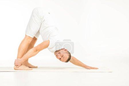 Photo pour Homme pratiquant le yoga et souriant à la caméra isolé sur blanc - image libre de droit