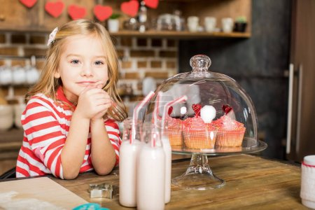 Photo for Adorable little girl sitting at table with milkshakes and delicious cupcakes - Royalty Free Image