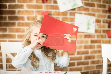 Photo for Cute little girl holding red paper and looking through cutting heart - Royalty Free Image