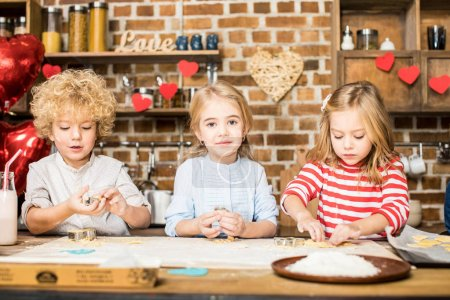 Photo for Three adorable little children cooking biscuits from unbaked dough - Royalty Free Image
