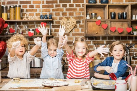 Photo for Adorable happy children cooking biscuits and showing hands in flour - Royalty Free Image