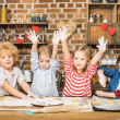 Four cute little children cooking biscuits and sho...