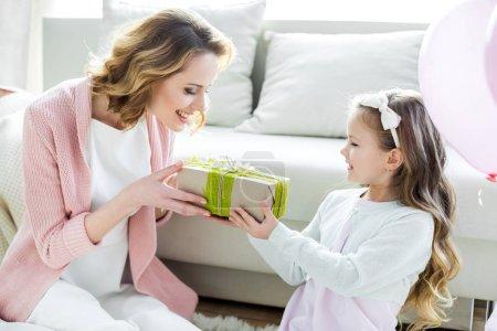 Photo pour Adorable petite fille présentant un cadeau à une mère heureuse le jour de la fête des mères - image libre de droit