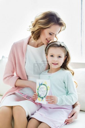 Beautiful mother and daughter with cards