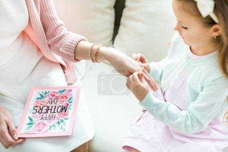 Foto de Vista parcial de niña linda poniendo joyas por parte de su madre en el día de las madres - Imagen libre de derechos