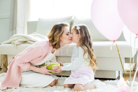 Photo for Adorable little girl presenting gift and kissing happy mother on Mothers Day - Royalty Free Image