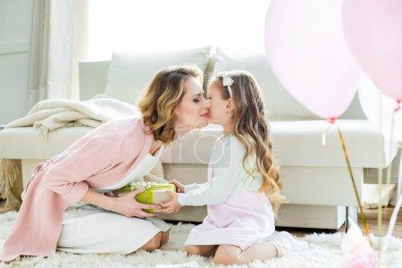Photo pour Adorable petite fille présentant cadeau et embrasser mère heureuse le jour de la fête des mères - image libre de droit