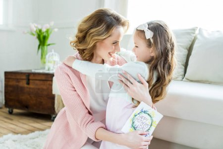 Photo for Happy mother hugging her adorable little daughter and holding greeting card for Mothers Day - Royalty Free Image
