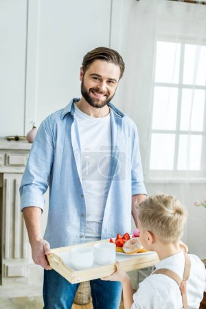 Father and son holding tray with breakfast