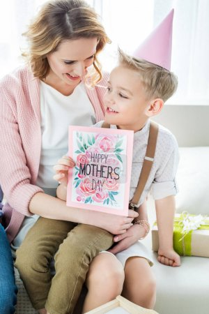 Photo for Smiling mother and son holding happy mothers day greeting card - Royalty Free Image