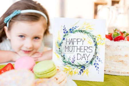 Photo for Close-up view of happy mothers day greeting card with pastries and little girl smiling at camera - Royalty Free Image