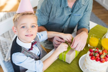 Photo for Little boy in cone hat packing gift with his father and looking at camera - Royalty Free Image