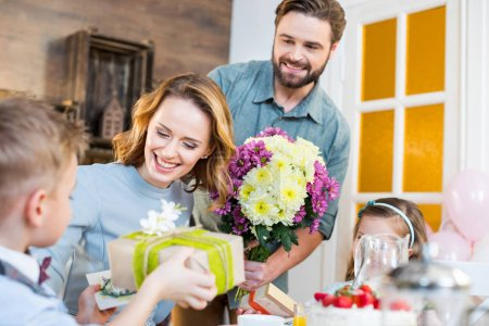 Photo for Happy young family celebrating Mothers Day with presents and flowers - Royalty Free Image
