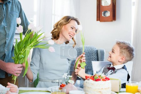 Photo for Young man and little boy gives fresh tulip flowers to happy woman - Royalty Free Image