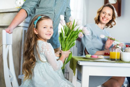 Photo for Happy little girl holding bouquet of fresh tulips and looking at camera - Royalty Free Image