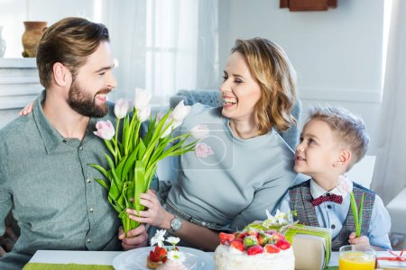 Photo for Happy family of three sitting at the table and celebrating Mothers Day at home - Royalty Free Image