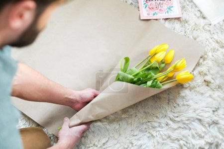 Photo for Partial view of man packing bouquet of fresh yellow tulips for Mothers Day - Royalty Free Image