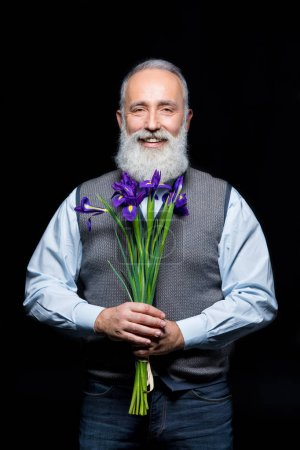 Photo pour Bearded senior man holding flowers and smiling at camera  isolated on black - image libre de droit