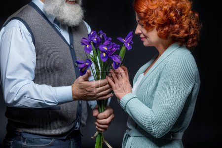 Photo for Beautiful mature couple with bouquet of fresh iris flowers  isolated on black - Royalty Free Image