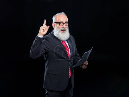 Photo pour Happy senior bearded businessman in eyeglasses holding documents and pointing up  isolated on black - image libre de droit