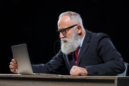 Photo for Concentrated senior bearded businessman sitting at table and using laptop  isolated on black - Royalty Free Image