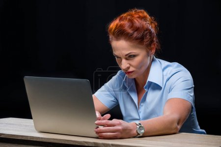 Photo for Mature concentrated businesswoman in formalwear using laptop  isolated on black - Royalty Free Image