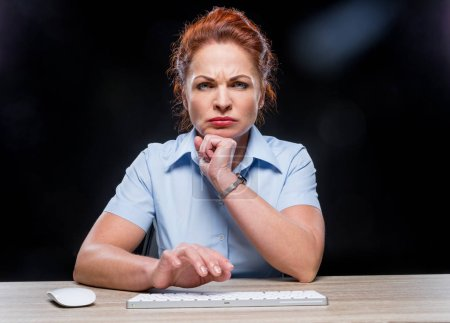 Photo for Angry mature woman typing on keyboard and looking at camera isolated on black - Royalty Free Image