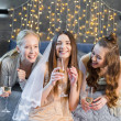 Happy young women drinking champagne at bachelorette party and smiling at camera