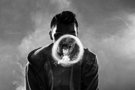Photo for Black and white photo of young bearded man vaping and making circle from smoke - Royalty Free Image