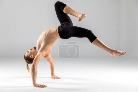 Photo for Young flexible shirtless man performing handstand on grey - Royalty Free Image