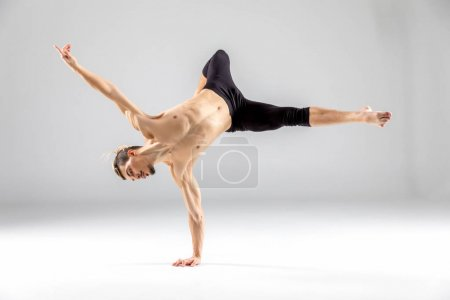 Photo for Young shirtless man performing dance movement standing on hand on grey - Royalty Free Image