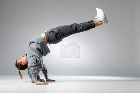Photo for Young handsome concentrated man performing dance movement - Royalty Free Image