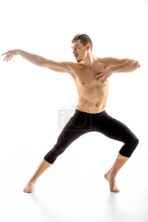 Foto de Young handsome shirtless man performing dance movement  isolated on white - Imagen libre de derechos