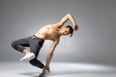Photo for Young handsome shirtless man performing dance movement - Royalty Free Image