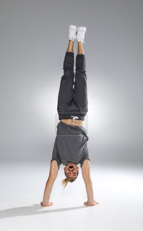 Photo for Happy young athletic man in sportswear performing handstand on white - Royalty Free Image