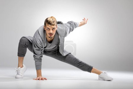 Photo for Young athletic male dancer in sportswear posing while looking at camera - Royalty Free Image