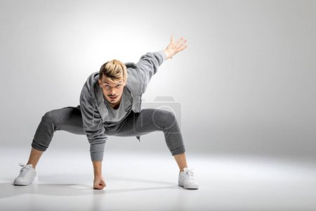 Photo for Young athletic male dancer in sportswear posing with fist hitting floor - Royalty Free Image