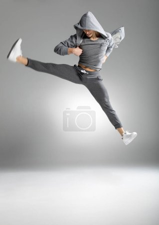 Photo for Handsome young athletic man in stylish clothes dancing on white - Royalty Free Image