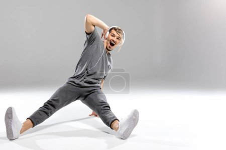 Photo for Happy young athletic man in headphones dancing and looking at camera - Royalty Free Image