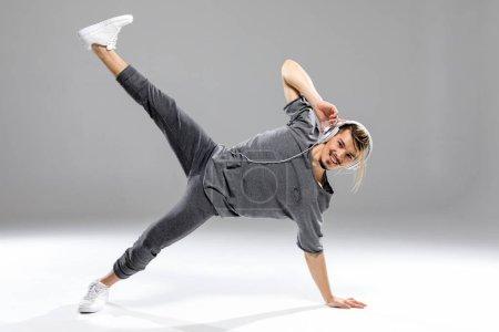 Photo pour Jeune danseur masculin athlétique dans les écouteurs posant et souriant à la caméra - image libre de droit