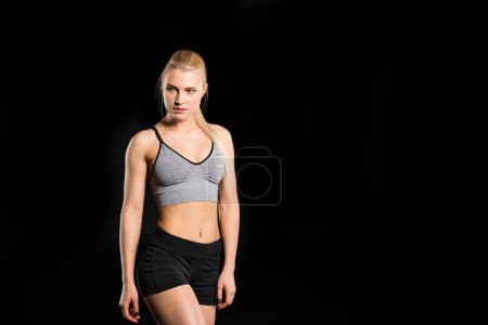 Photo for Beautiful young blonde woman in sportswear looking away  isolated on black - Royalty Free Image