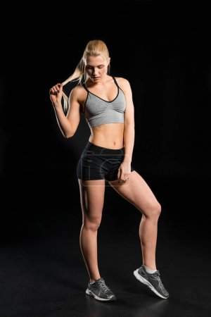 Photo for Full length view of beautiful young woman in sportswear posing  isolated on black - Royalty Free Image