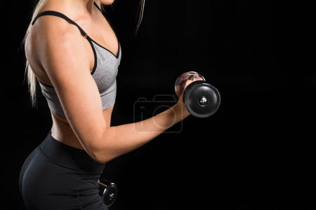 Photo for Partial view of young sporty woman exercising with dumbbells  isolated on black - Royalty Free Image