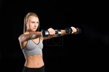 Photo pour Young blonde woman in sportswear exercising with dumbbells isolated on black - image libre de droit